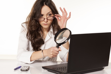 private detective: suspicious secretary in white shirt did found something on her laptop with a magnifying glass