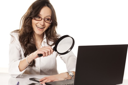 investigating: happy secretary in white shirt did found something on her laptop with a magnifying glass