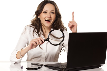 happy girl in white shirt did found something on her laptop with a magnifying glass