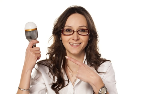 Smiling girl shows on the latest generation of energy-saving light bulbs Stock Photo - 18383696