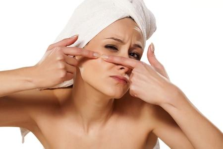Renfrogné fille écrase son acné avec une serviette sur la tête Banque d'images - 18383705
