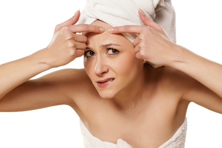 pimples: Scowling girl squeezes her acne with a towel on her head