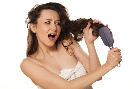 girl is nervous because of problems with combing on white background