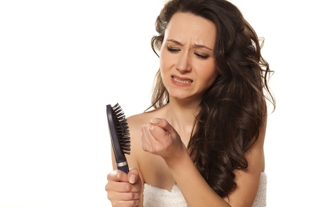 hairbrush: unhappy and sad girl because of her loss of hair Stock Photo