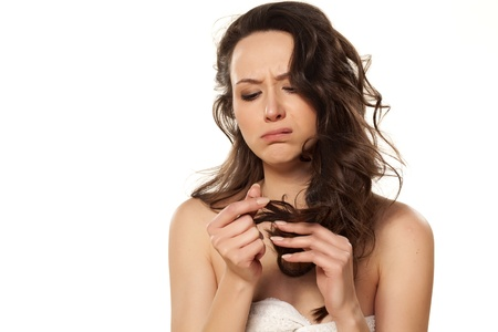 unhappy and sad girl because of her damaged hair Stock Photo