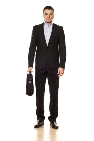 standing man: attractive businessman with a laptop bag posing on a white background