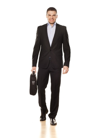 studio shot of attractive smiling young businessman walking with a laptop bag photo