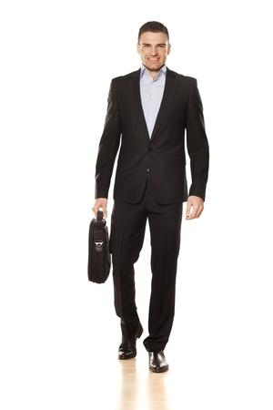 tourné en studio d'attrayant jeune homme d'affaires souriant marcher avec un sac d'ordinateur portable Banque d'images