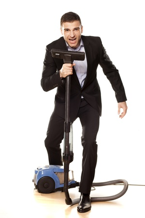 Young attractive businessman with a vacuum cleaner photo