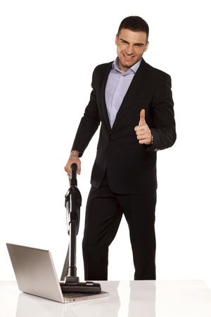 smiling and attractive young businessman vacuum cleans his laptop and showing thumbs up photo