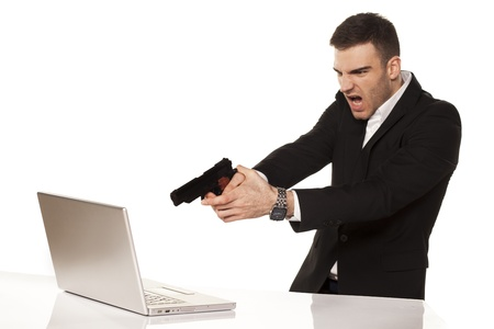 mad and angry young businessman destroying his laptop using guns
