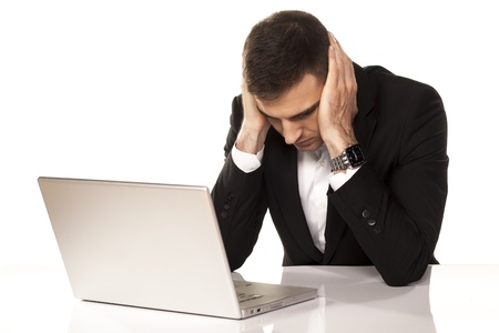 desperate young businessman leaning on both hands behind his laptop Stock Photo