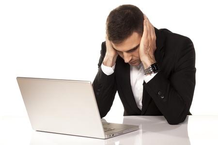 wanhopige jonge zakenman leunend op beide handen achter zijn laptop
