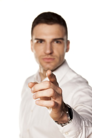 angry attractive young man pointing a finger towards you photo