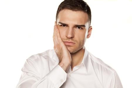 dolor de muelas: un hombre joven con un dolor de muelas en el fondo blanco Foto de archivo