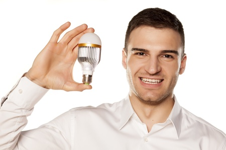 cree: smiling attractive young man, holding the LED bulb in his hand