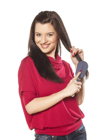 beautiful brunette with blue eyes in a red blouse comb her hair Stock Photo