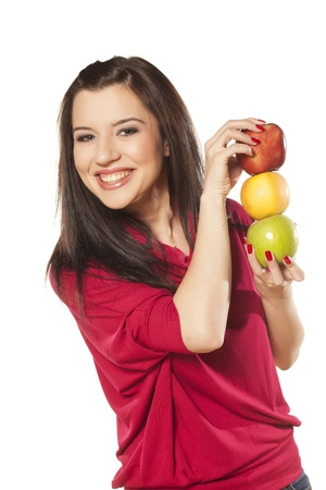smiling beautiful dark-haired girl with blue eyes shows three different apples photo