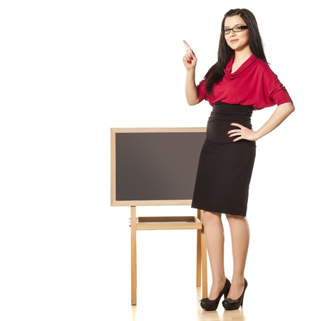 beautiful dark-haired girl with glasses, standing behind an empty table and shows something in the empty space photo