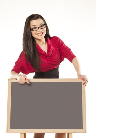 beautiful dark-haired girl with glasses, standing behind an empty table to show something photo