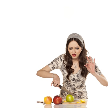 clumsy: nice and desperate housewive try to Slice an apple on the table Stock Photo