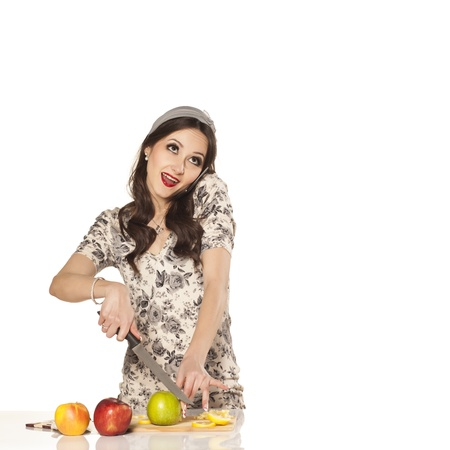 Smiling pretty housewife simultaneously cutting an apple and explains the recipe over the phone photo
