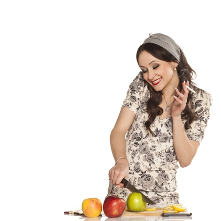 simultaneously: Smiling pretty housewife simultaneously cutting an apple and smoking a cigarette