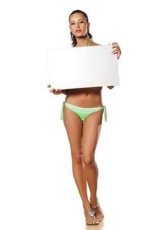 sandals: smiling pretty and beautiful young brunette in a bikini holding a blank sign on white  Stock Photo