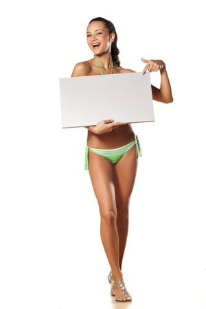 smiling pretty and beautiful young brunette in a bikini holding a blank board on which points a finger photo