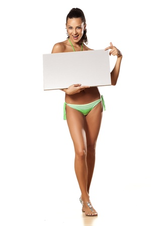 smiling pretty and beautiful young brunette in a bikini holding a blank board on which points a finger