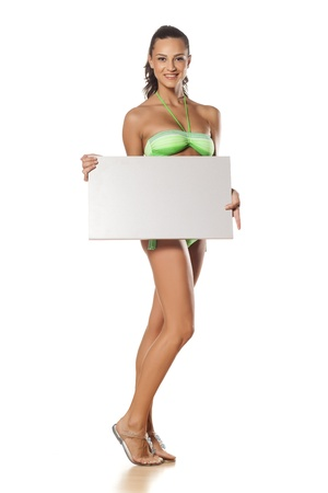 bikini sexy: smiling pretty and beautiful young brunette in a bikini holding a blank sign on white  Stock Photo