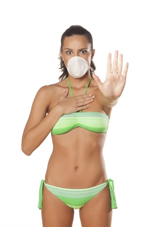 dust mask: beautiful brunette with a breathing mask in a bikini showing stop sign with her hand  Stock Photo
