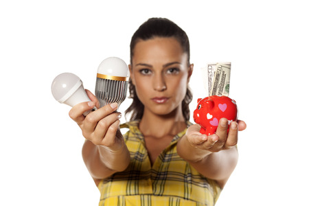 Serious girl shows that you can save money with LED bulbs photo