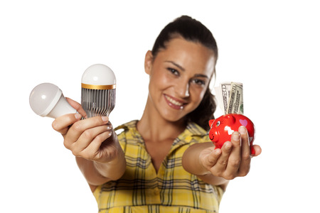 cree: Smiling girl shows that you can save money with LED bulbs Stock Photo