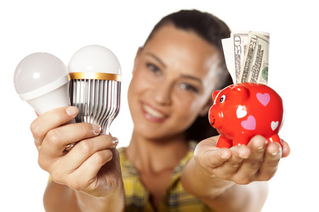 Smiling girl shows that you can save money with LED bulbs Stok Fotoğraf