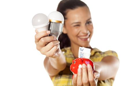 tu puedes: Muchacha sonriente que muestra que usted puede ahorrar dinero con bombillas LED Foto de archivo