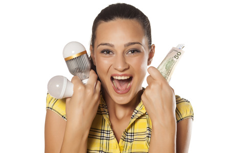 Smiling girl shows that you can save money with LED bulbs photo