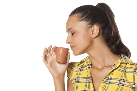 beautiful young brunette enjoys the smell of her coffee from the machine Stock Photo - 22725033