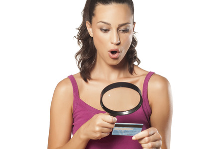 woman credit card: Suspicious girl looking her credit card using the magnifying glass