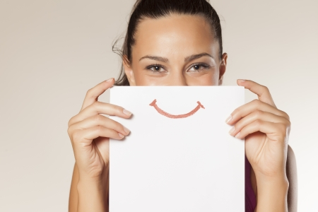 happy and smiling girl with a smile painted on paper photo