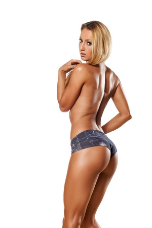 Rear view of pretty and muscular topless girl with long blond hair