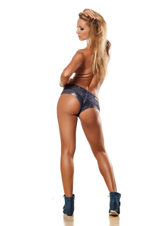 Rear view of pretty and muscular topless girl with long blond hair photo