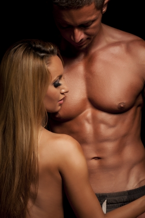 Young and fit topless couple in an embrace on dark background Stock Photo
