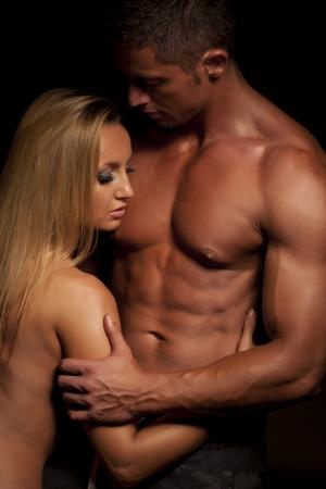 Jeunes et en bonne couple topless dans une étreinte sur fond sombre Banque d'images
