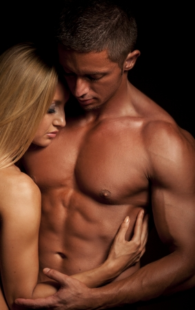 Young and fit topless couple in an embrace on dark background photo