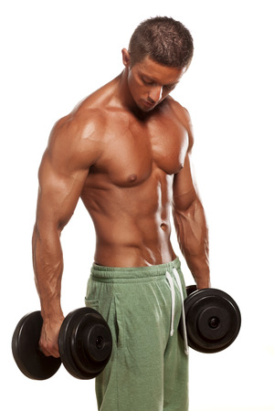 muscular super-high level  handsome man holding weights and posing on a white background