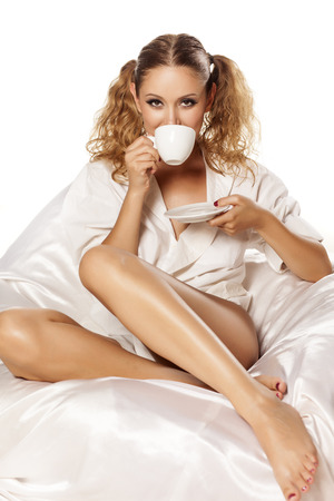 beautiful sexy girl in a white shirt enjoys her morning coffee photo
