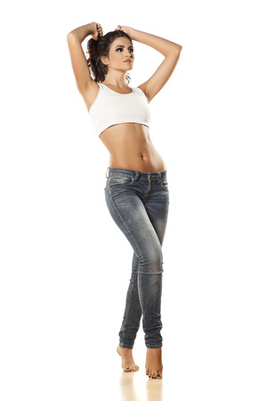 young woman in jeans with bare belly on white background photo