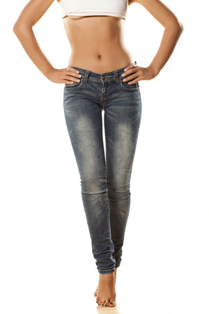 Ladies bare stomach and long legs in jeans on a white background Stok Fotoğraf