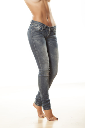 Ladies bare stomach and long legs in jeans on a white background photo